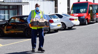 Abdul Awan, a Dial-a-Ride driver, carrying food as part of the changed service delivered by TfL during the pandemic